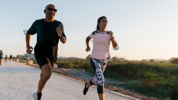 A man and a woman going for a run outdoors. The man is wearing all black and the woman is wearing pink and blue gym gear.