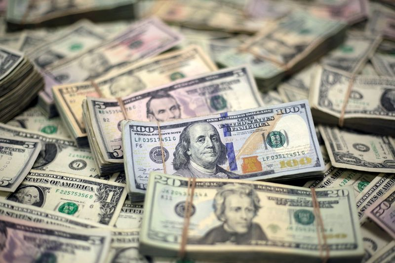 Dollar hovers near one-week low as Evergrande questions persist