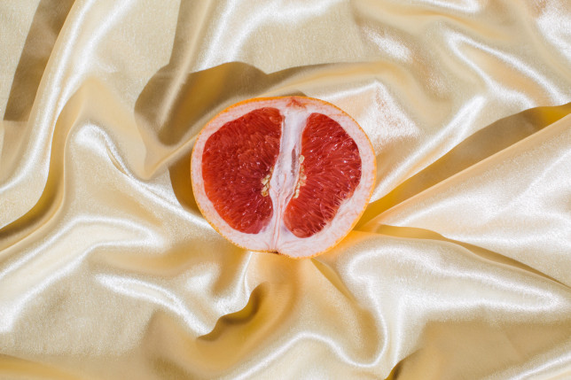 Fresh grapefruit on beige soft silk fabric background. Sex concept. Women's health, sexuality, erotic tension. Female vagina and clitoris symbol.