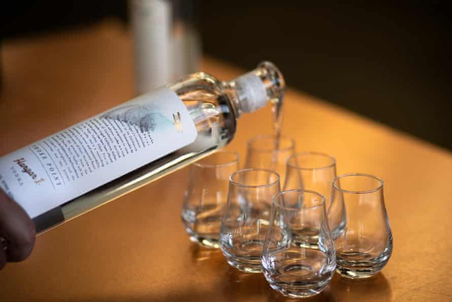 A bottle of Smoke Point vodka is being poured into six glasses lined up on a bar.