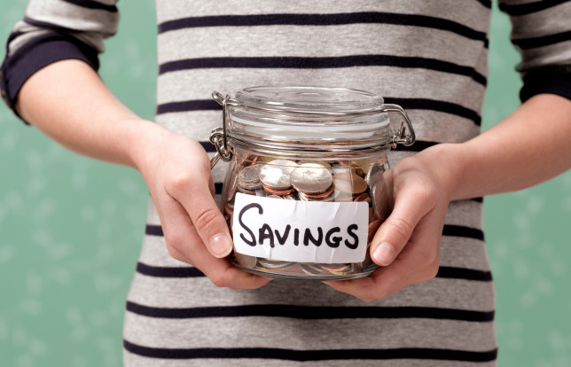 Person holding savings jar full of coins