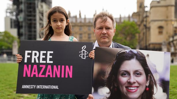 Richard Ratcliffe and his daughter Gabriella hold signs in Parliament Square to mark the 2,000th day Nazanin Zaghari-Ratcliffe has been detained in Iran