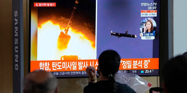 People watch a TV showing a file image of North Korea's missiles launch during a news program at the Seoul Railway Station in Seoul, South Korea, Tuesday, Sept. 28, 2021. (AP Photo/Ahn Young-joon)
