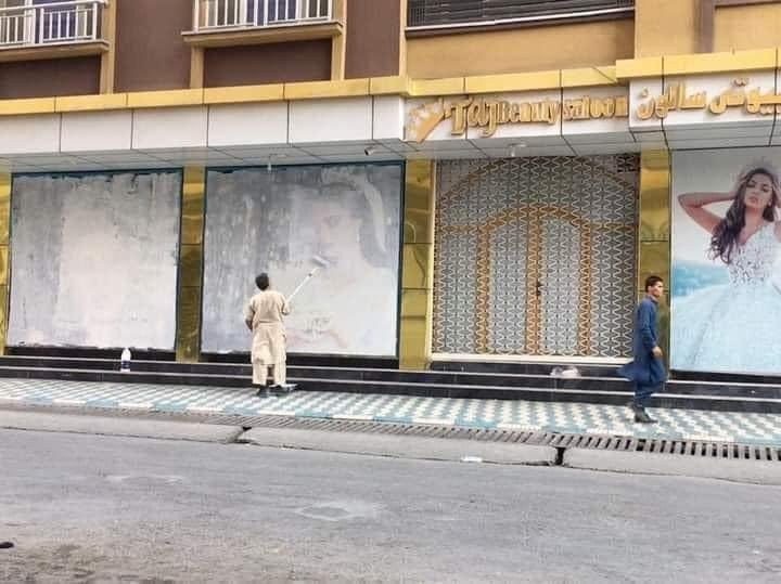 Images of women outside a bridal shop are painted over in Kabul