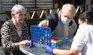 Boris Johnson plays a board game with care home residents in east London. Photograph: Paul Edwards/WPA/Getty