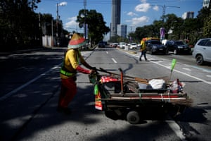 Alejandro Galasao, 58, street sweeper, pushes a cart with cleaning supplies in Quezon City