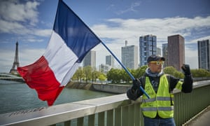 A Gilet Jaune or 'Yellow Vest' protestor holds a French Tricolor flag last weekend.