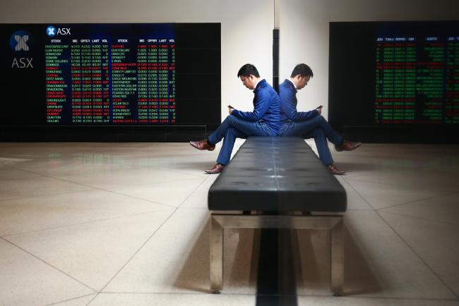 © Bloomberg. A man looks at his phone as an electronic board displays stock information at the Australian Securities Exchange, operated by ASX Ltd., in Sydney, Australia. Photographer: Brendon Thorne/Bloomberg