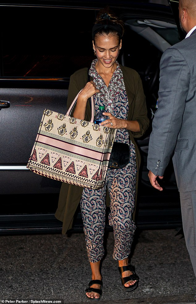 Simply stunning: The 38-year-old actress and mogulrocked a sheer patterned jumpsuit along with an olive green duster coat and a pair of on-trend black leather Birkenstock sandals