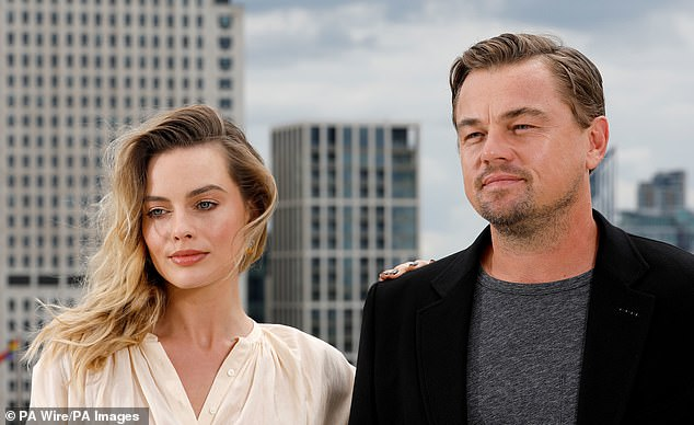 Friends: Margot placed one hand on Leo's shoulder as they posed for more pictures together