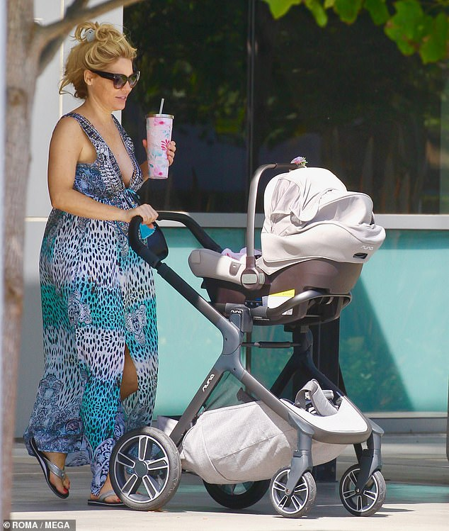 There's mommy! Rossi, 40, stepped out sans makeup in a flowing aqua-colored maxi dress with a cheetah print and plunging neckline