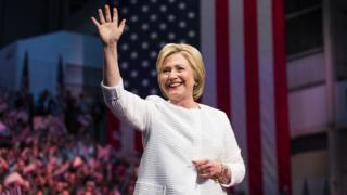 Hillary Clinton waving to crowds in front of the US flag