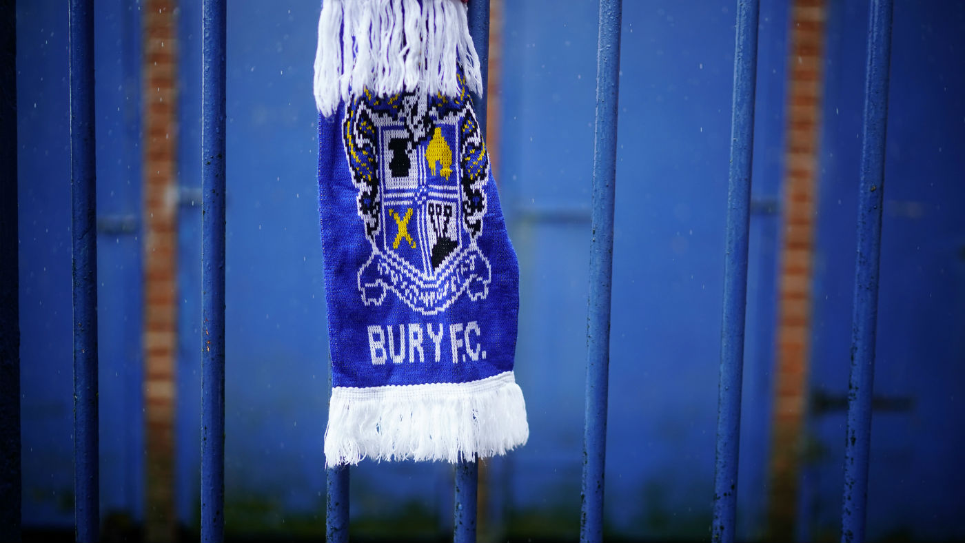 Bury FC scarves hang on a fence outside the EFL League One club's Gigg Lane stadium