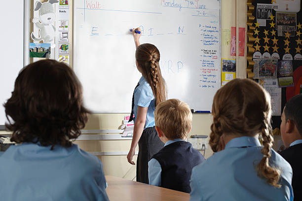 Young student in front of her classmates in the classroom drawing on a whiteboard