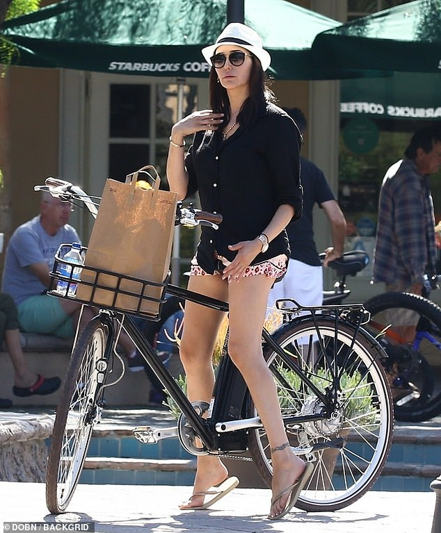 Glamorous: Lauren put on a leggy display for the outing as she sported a loose black shirt and floral shorts teamed with gold flip flops