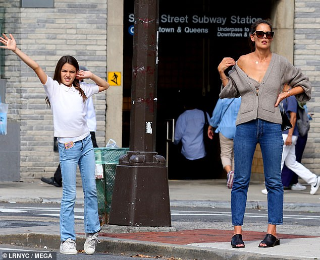 Helping hand: Suri was seen helping her mom, with one hand raised high in the air as the two attempted to hail a cab