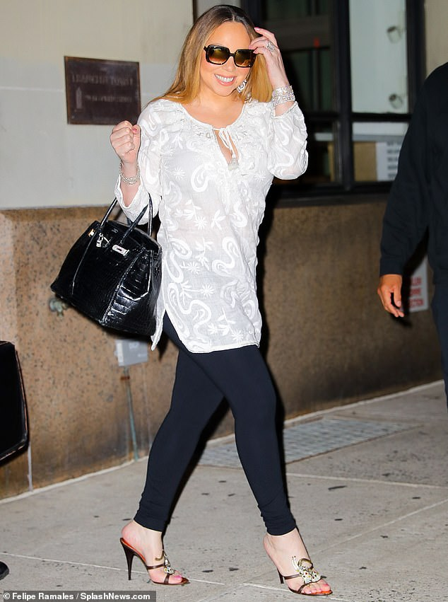 Always glam: Mariah looked slender in her chic outfit. He had on a long white top that tied in the front with a keyhole