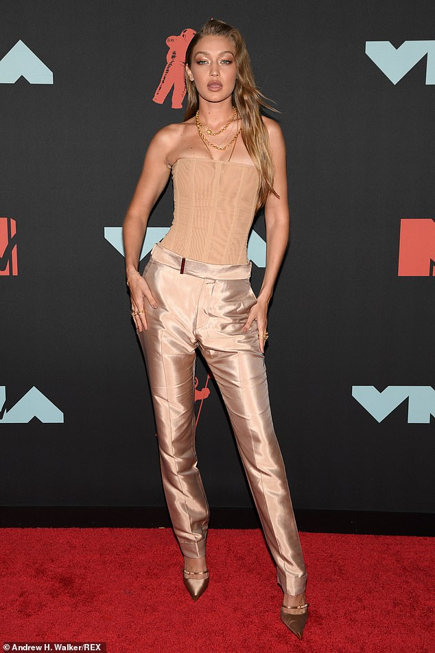 Shine bright:For the star studded night, Gigi wore shining bronze colored silk slacks paired with a tan bustier top