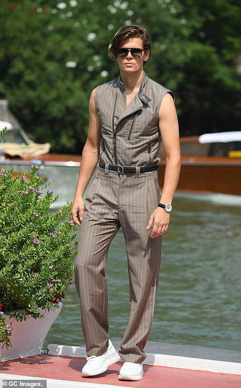 Slick: Model Alessandro Egger displayed his muscular arms in a grey pinstripe jumpsuit and white platform trainers
