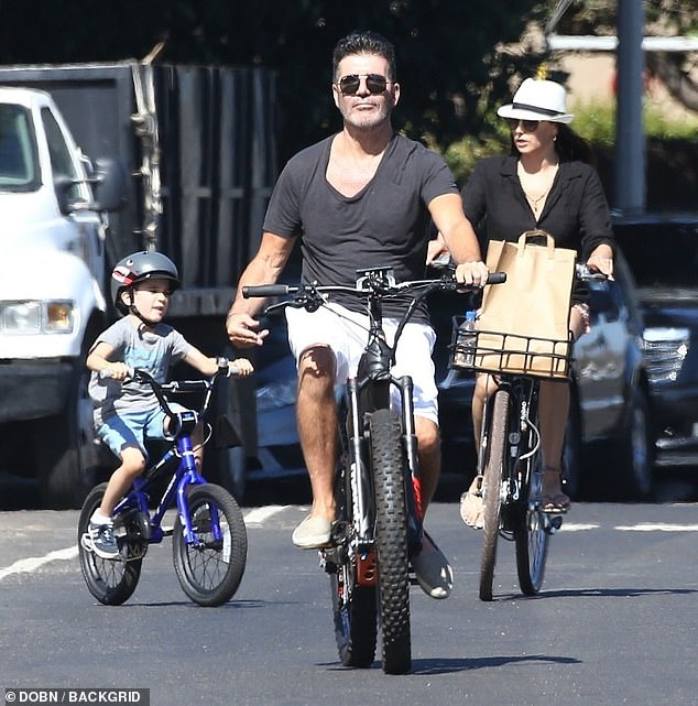 Happy:The music mogul cut a relaxed figure as he headed for lunch in the sunshine with his girlfriend and son