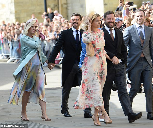 Glam arrival: Walking into the church hand-in-hand with her other half, she donned a pair of buckle-detailed mules with a fuchsia pink mini leather handbag