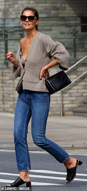 Crossing the road: Katie paired the look with oversized black sunglasses and black mules that had a small heel