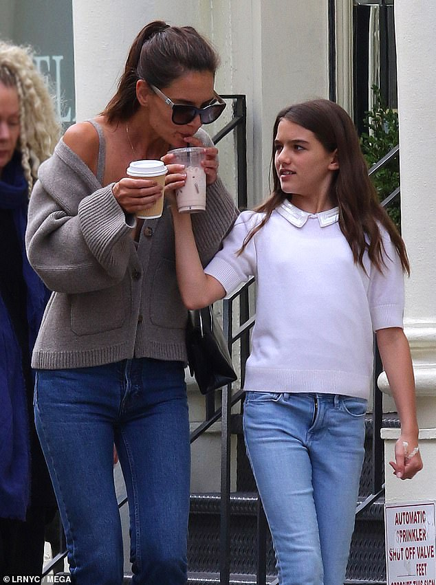 Sipping tea: She wore her brown tresses up in a straight back ponytail, accessorizing with a simple silver necklace and silver bracelets, one on each arm