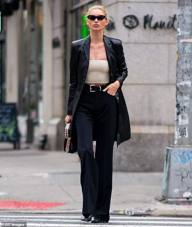 Hitting the street:Sweeping her platinum hair back into a bun, she wrapped herself in a long black leather overcoat and popped on a pair of cat-eye sunglasses