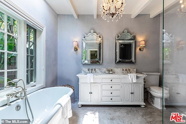 Bathing in style: The adjoining master bathroom has a stand alone tub, wall-to-ceiling glass shower and a chandelier