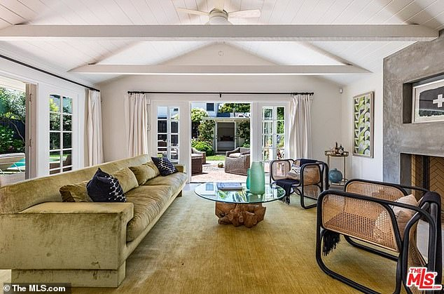Relaxing: An adjoining living room has French doors along two walls opening out onto the garden as well as a large fireplace