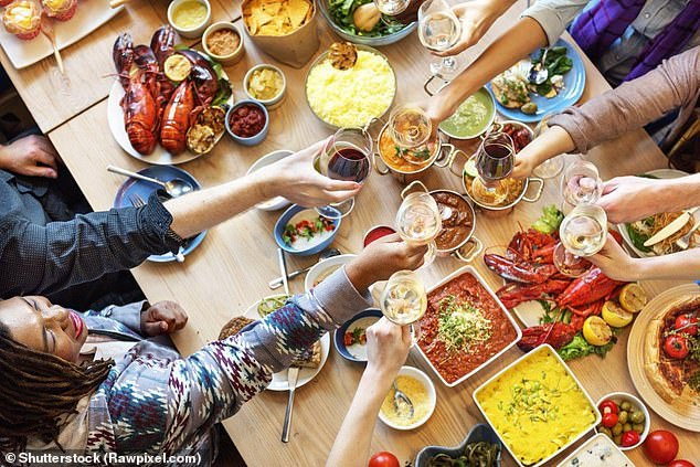 One reason for people eating more when they were in groups was that it is seen as more socially acceptable to gorge oneself than when they're alone, scientists said (stock image)