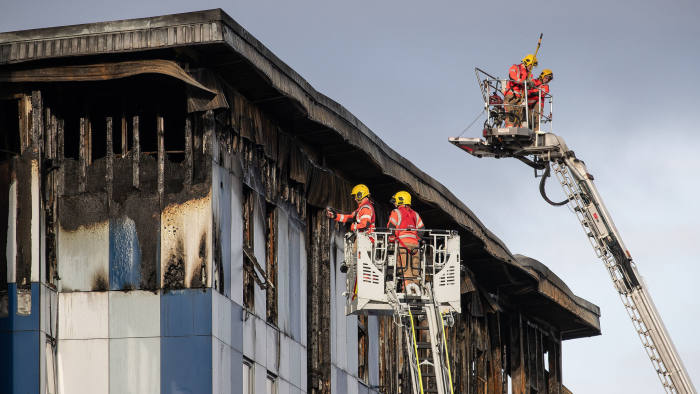 © Licensed to London News Pictures. 16/11/2019. Bolton, UK. Firefighters examine cladding at the scene where a fire broke out overnight (15th/16th November 2019) at a block of flats known as