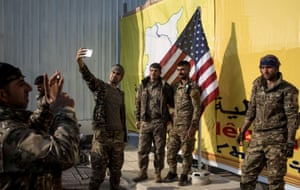 Fighters from the Kurdish-led Syrian Democratic Forces pose for a photo with the US flag after a ceremony announcing the defeat of Islamic State in Baghouz in March.