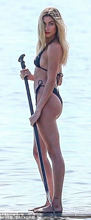 Shape on water: She showed off her incredible figure in a tiny black string bikini as she hopped on a paddle board