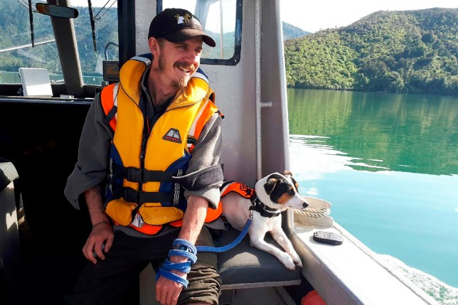 In this undated photo released by New Zealand Department of Conservation, Flint, the rat-detecting dog and its handler Richard Johnston ride on a boat near the Tennyson Inlet Islands in New Zealand. Flint was on a remote island between New Zealand and Antarctica as part of a mission involving the military when a sealion charged at him. He got spooked and ran away, and couldn???t be found by a military helicopter. The team was forced to leave him behind on Wednesday, Nov. 27, 2019. But he was rescued on Friday, Nov. 29 after a helicopter crew flew to the island and found he???d walked back to the base. (New Zealand Department of Conservation via AP)