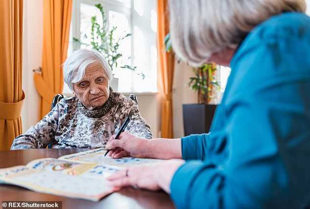 Woman taking care of elderly woman doing crossword puzzle (stock)