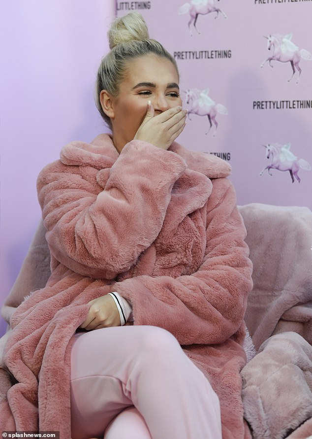 Surprised: The former Love Island star turned heads in a faux fur pink coat as she laughed and joked with delighted winners of her competition