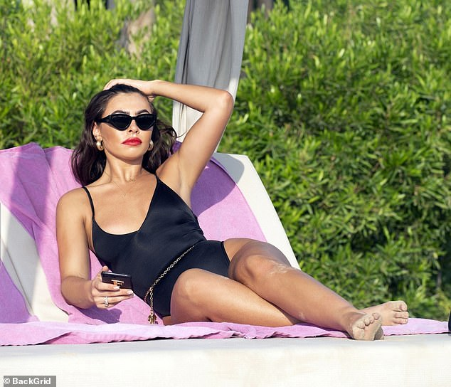 Stunner: The Bonnie & Clyde boutique owner, 24, oozed retro Hollywood glamour in a simple black swimsuit with a Chanel belt and a slick of red lipstick