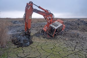 An excavator machine sinking in degraded wetland in the Danube Delta Biosphere Reserve