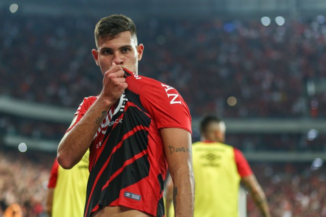 Bruno Guimarães kisses the badge of his club after scoring