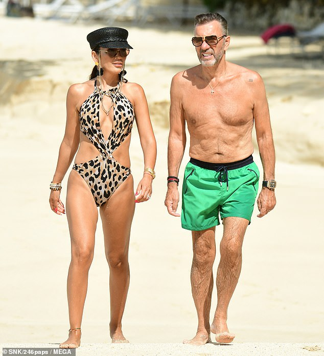 Happy: Duncan Bannatyne, 70, and his stunning wife Nigora Whitehorn, 39, were enjoying their festive break as they hit the beach for a spot of sunbathing on Sunday