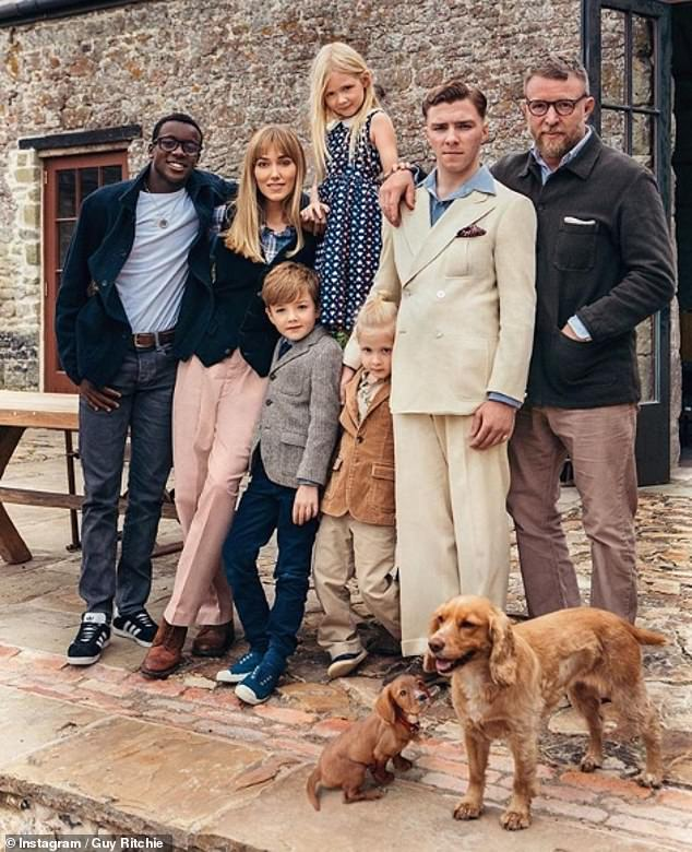 All together: Guy Ritchie, 51, shared a sweet snap of his family, including his five children, to mark Christmas Day on Wednesday. Pictured left to right is David Banda, 14, wife Jacqui Ainsley, 38, Rafael, eight, Rivka, seven, Levi, five, Rocco, 19, and Guy