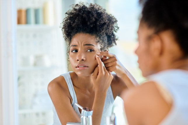 young woman inspecting her face in the bathroom mirror