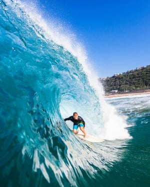 Surfer tube rides inside large hollow crashing blue ocean wave swimming water photo
