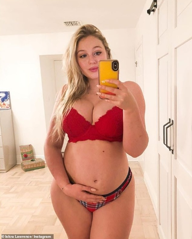 Festive shoot: Iskra Lawrence shared a number of festive snaps on Wednesday, posing in a red bra and tartan knickers as she showed off her blossoming baby bump
