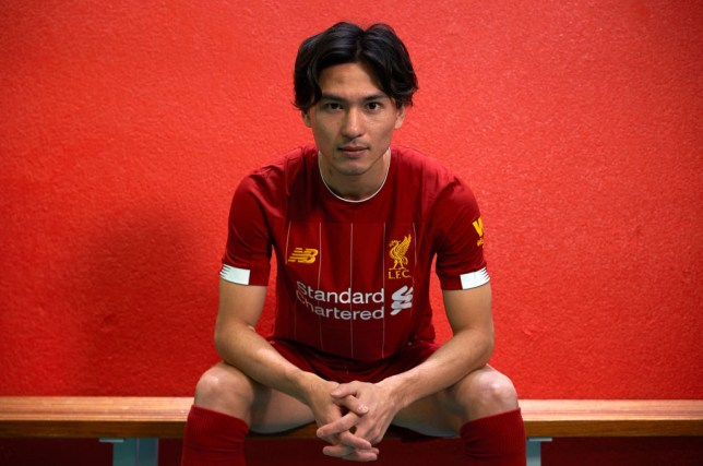 Takumi Minamino poses in a Liverpool kit after signing for the Reds