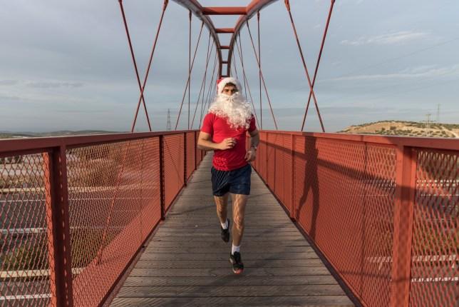 Athlete In Santa Hat Running On Footbridge Against Sky