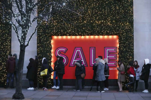 Shoppers in front of a Boxing Day sales sign