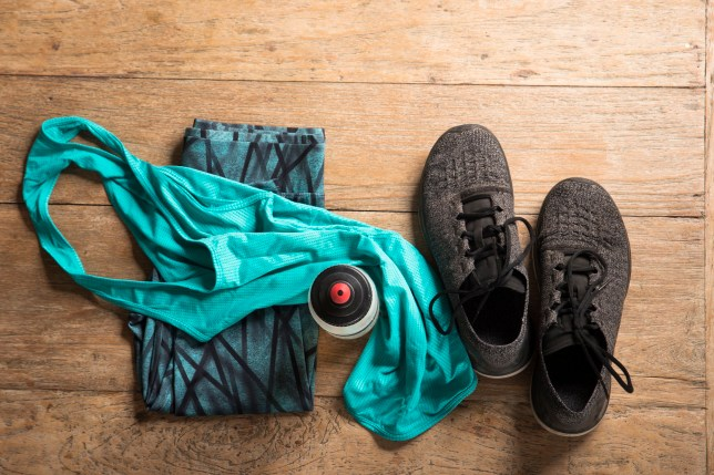 Gym clothing spread out on a wooden floor including a top, leggings, water bottle and trainers
