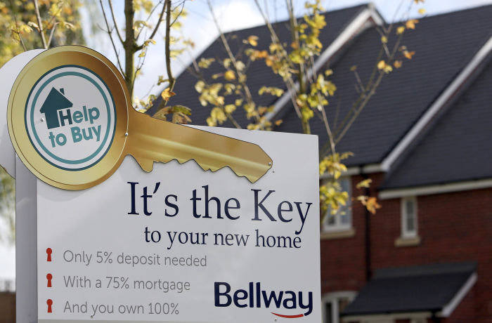 "An advertisement for the U.K. Government's new ""Help to Buy"" scheme sits outside a row of new residential homes at a Bellway Plc real estate site in Northampton, U.K., on Thursday, Oct 10, 2013."